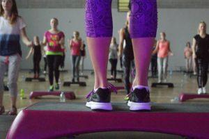 nogi na stepie, w tle ćwiczące osoby